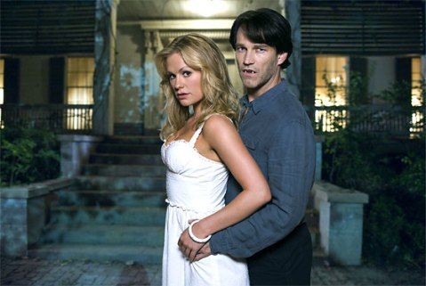 Sookie, wearing a white dress, and Bill, wearing a gray shirt and dark slacks with fangs out, are standing next to each other in front of a house.